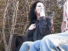 Brunette babe giving blowjob while smoking
