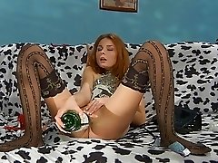 Drunk redhead babe in black stockings fingers her pussy on couch