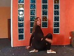 Flexible teen ballerina in black body stocking streching